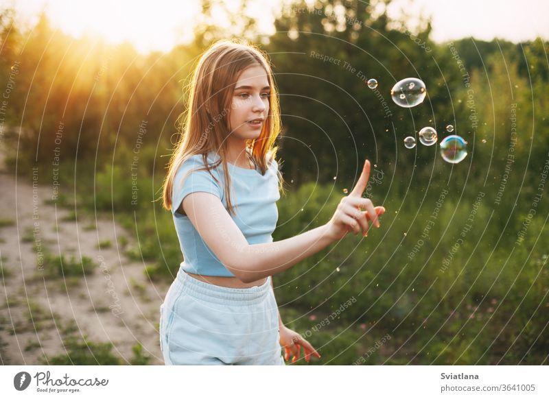 Ein süßes Mädchen mit einem schönen Lächeln fängt Seifenblasen auf dem Hintergrund eines wunderschönen Sonnenuntergangs ein. Blasen wenig blasend niedlich Kind