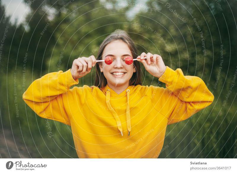 Ein lächelndes Mädchen in einem knallgelben Pullover hält einen knallroten Lolli in der Hand. Sommerliche Natur Bonbon Lollipop lustig hell Gesundheit Lifestyle