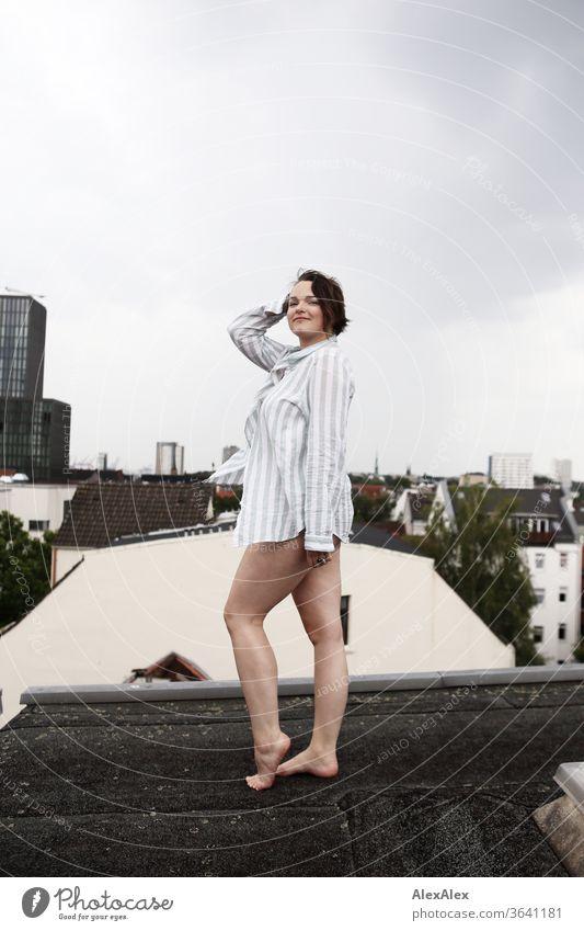 Portrait einer jungen, barfüßigen Frau auf einem Dach junge Frau Top windig Haare brünett schön intensiv Jugendliche 18-25 Jahre bauchfrei weiblich sportlich