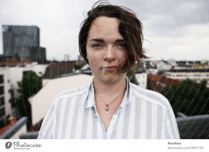 Portrait einer jungen, sommersprossigen Frau auf einem Dach junge Frau Top windig Haare brünett schön intensiv Jugendliche 18-25 Jahre Dekolleté