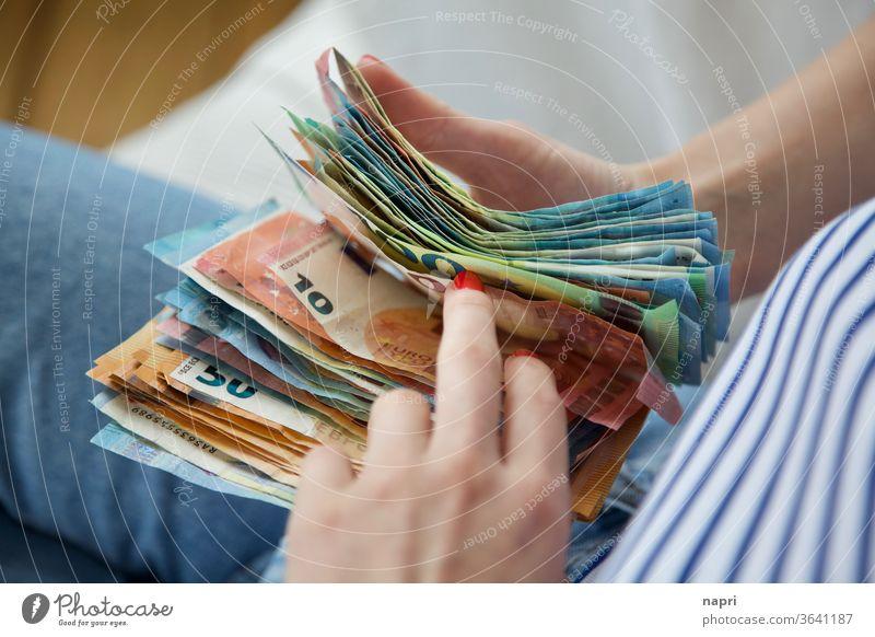 Reisekasse | Junge Frau hält einen Stapel Geldscheine in den Händen und zählt durch. Euro Bargeld zählen sparen Einkommen Reichtum bezahlen kaufen sparsam reich