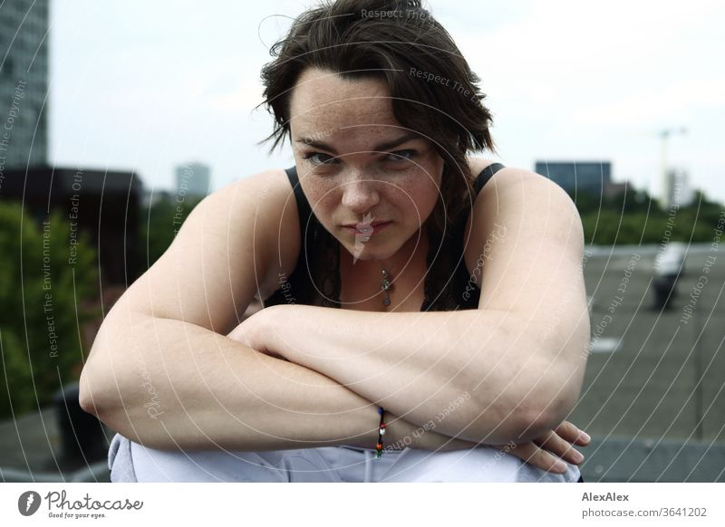 Portrait einer jungen, sommersprossigen Frau auf einem Dach junge Frau Top Haare brünett schön intensiv Jugendliche 18-25 Jahre Blick in die Kamera weiblich