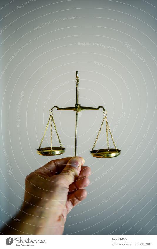 Hand hält eine Waage fest und vergleicht beide Seiten miteiander Zeit Geld Konzept Gleichgewicht Gewicht Gerechtigkeit Ehrlichkeit Justiz u. Gerichte Justitia