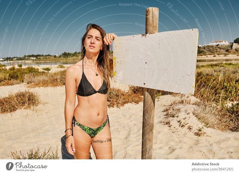 Fröhliche Reisende im Badeanzug am Strand MEER Zeichen Frau Bikini Tourismus Strandpromenade Urlaub Sommer Sand schlank reisen Feiertag Badebekleidung Küste