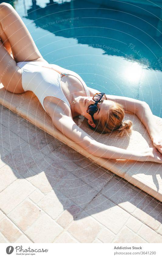 Schlanke Frau im Badeanzug entspannt am Pool Sonnenbad Bräune Beckenrand sich[Akk] entspannen Urlaub Lügen sonnig ruhen Resort Sommer Windstille Feiertag Kälte