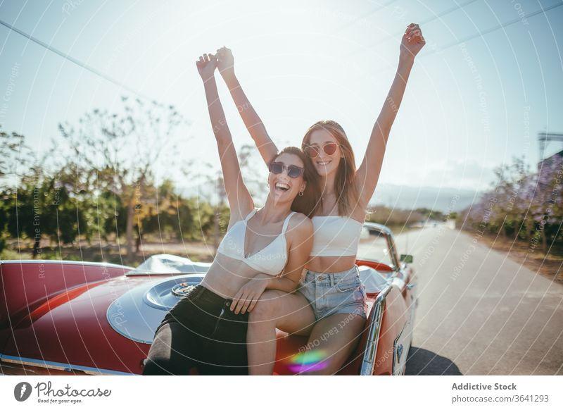 Entzückte Freundinnen haben im Sommer Spaß auf der Straße Urlaub genießen Frauen Cabriolet PKW sorgenfrei heiter Zusammensein Feiertag Lächeln Glück reisen
