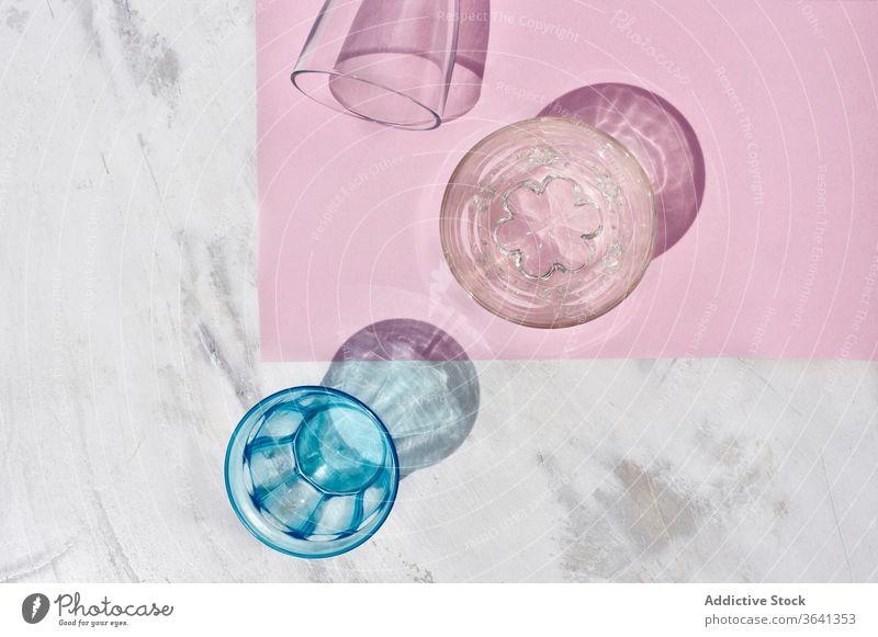 Brillensatz auf rosa Tisch Glas Glaswaren Kulisse sortiert Schatten Atelier Zusammensetzung farbenfroh Kristalle kreativ hell Farbe durchsichtig glänzend