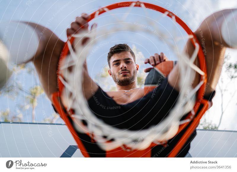 Basketballspieler sitzt auf einem Korb auf dem Spielplatz Reifen Mann Sportler Spieler Training Ball Gesundheit männlich gutaussehend professionell Aktivität