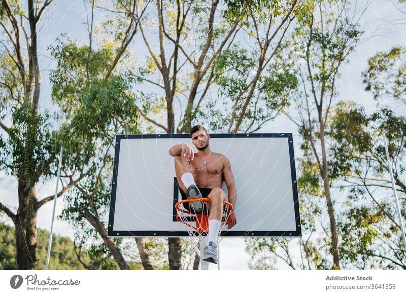 Basketballspieler sitzt auf einem Korb auf dem Spielplatz Reifen Mann Sportler Spieler Training Gesundheit männlich gutaussehend professionell Aktivität Übung