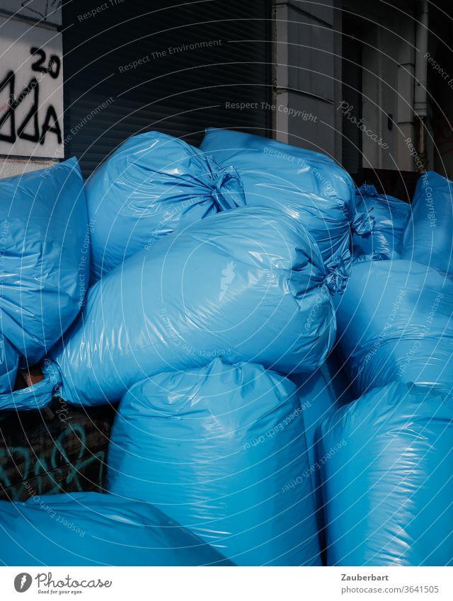 Blaue Müllsäcke aus Plastikfolie stapeln sich auf der Straße Müllsack Abfall Stapel wegwerfen Umwelt Müllentsorgung Recycling entsorgen prall Falten Müllabfuhr
