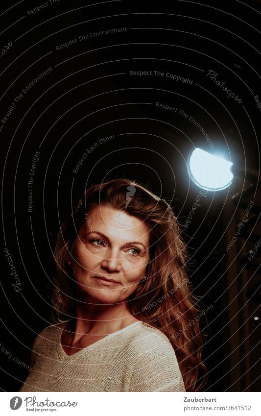 Schöne Frau bei einem Shooting im Fotostudio mit Scheinwerfer vor dunklem Hintergrund schön Studio Photo-Shooting Beleuchtung Strahler Pullover brünett Haare