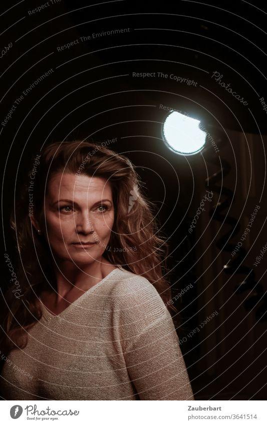 Schöne Frau schaut ernst bei einem Shooting im Fotostudio mit Scheinwerfer vor dunklem Hintergrund (2) schön Studio Photo-Shooting Beleuchtung Strahler Pullover