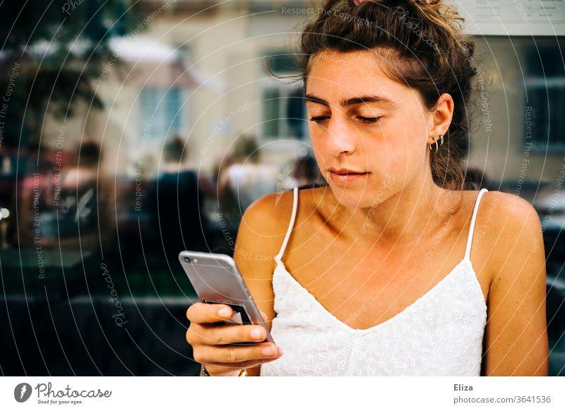 Junge Frau sitzt draußen in einem Café und sieht in ihr Smartphone Sonne Handy lesen beschäftigt junge Frau Telefon Mädchen konzentriert Lifestyle Sommer