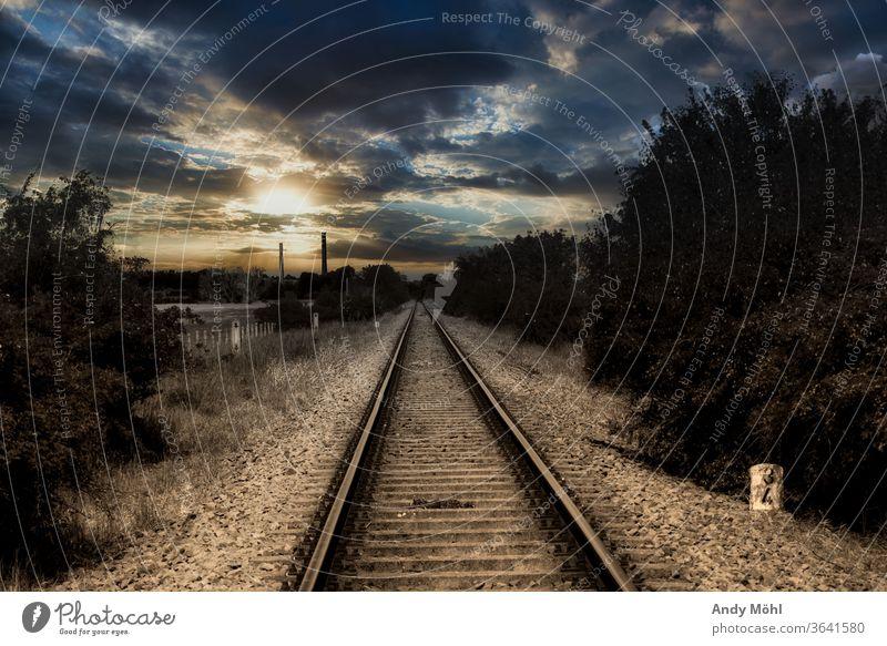 Einsame Bahnstrecke in der Mitte von Nirgendwo Landschaft Bahnschienen Wolken dunkel draußen Schwarzweißfoto Sonnenuntergang Sonnenlicht mystisch Baum Stein