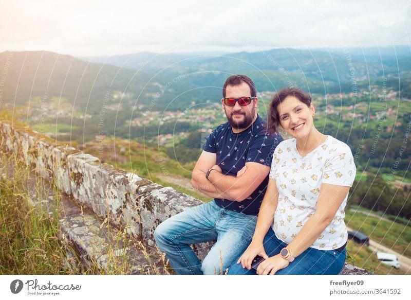 Ein schwangeres heterosexuelles Paar posiert vor einer schönen Landschaft Liebe Freunde Frau Herbst Winter Gras wild Wildgras Natur Touristen wandern Galicia