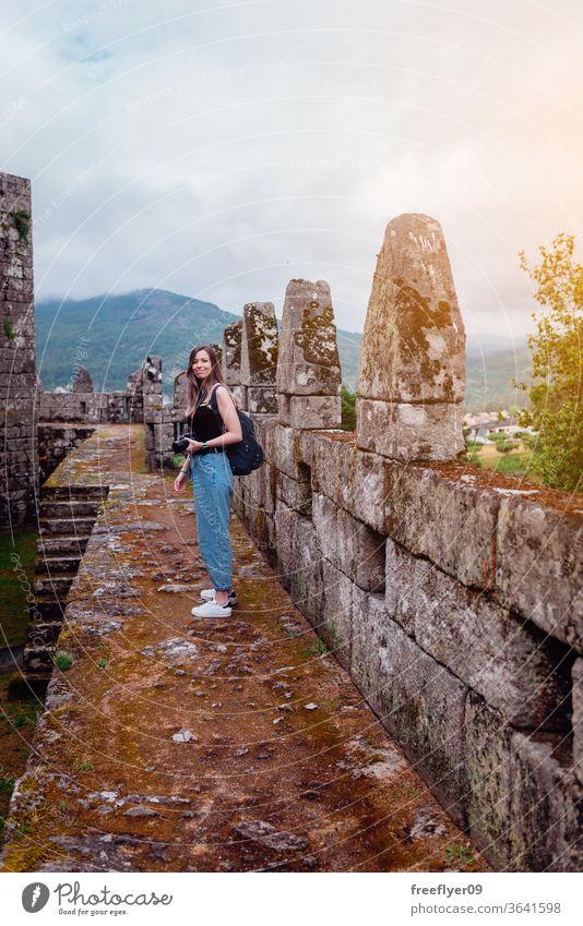 Weibliche Touristin mit Kamera Fotokamera Fotograf Frau Kaukasier blond Festungsmauern mittelalterlich Zinnen Burg oder Schloss Tourismus reisen Verlassen