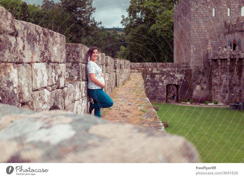 Schwangere Frau auf den Ruinen einer mittelalterlichen Burg schwanger in die Kamera schauen Burg oder Schloss Festungsmauern Zinnen Tourismus reisen Verlassen