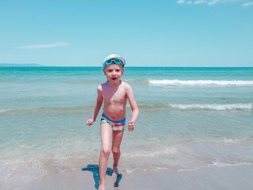 Glücklicher kleiner lächelnder Junge läuft an einem sonnigen Sommertag am Meeresufer entlang Ufer MEER Strand Sonne Himmel blau jung Lifestyle Sand im Freien