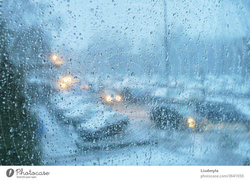 Regentropfen auf einem durchsichtigen Glas. Abends Blick auf den Stadtverkehr. Tröpfchen Autos Marmelade Fahrzeug Verkehr glühend Großstadt Dämmerung Unwetter