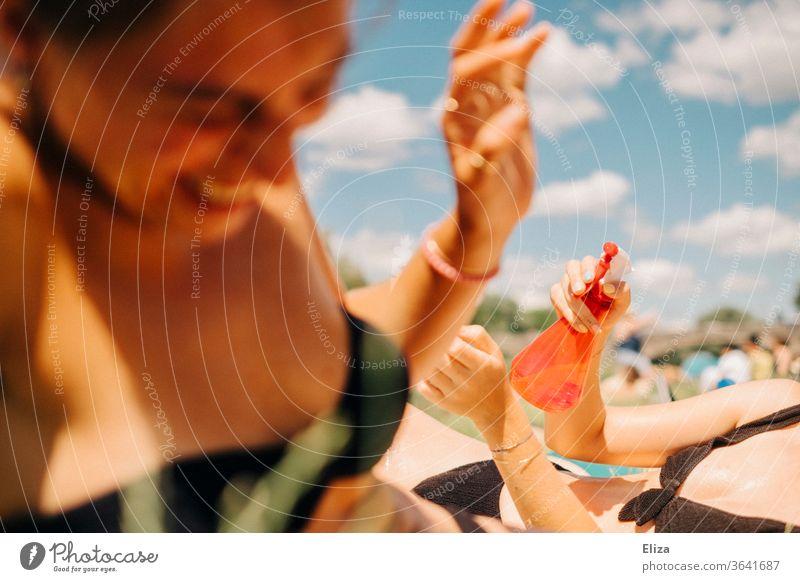 Zwei junge Frauen beim Baden, die Spaß haben und sich mit Wasser aus einer Sprühflasche bespritzen. Sommer und Lebensfreude. abkühlen Mädchen See Schwimmbad