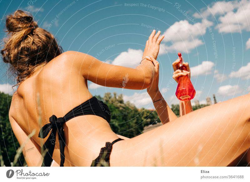 Zwei junge Frauen , die sich amüsieren und sich mit Wasser aus einer Sprühflasche bespritzen baden Sommer Spaß kühlen Mädchen sich[Akk] sonnen Bikini Sonne