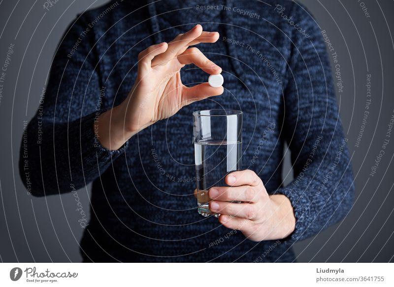 Mann bereit, die Pille in Wasser aufzulösen. Lösliche weiße Pille und ein Glas Wasser in der Hand. Brausetablette Aspirin in einem Glas Wasser Business jung