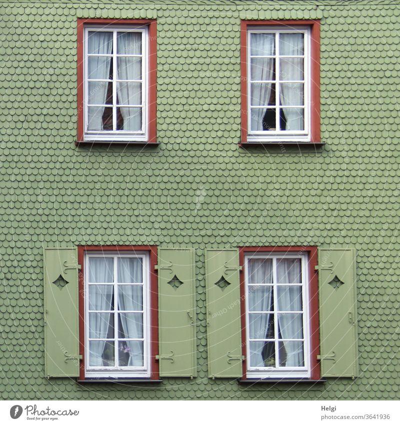 grüne Schindelfassade mit Fenstern und Fensterläden | Symmetrie Fassade Haus Gebäude Schindeln Menschenleer Außenaufnahme Architektur Wand Bauwerk Stadt