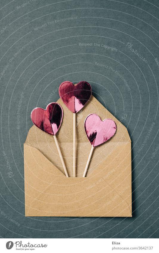 Drei rosa Herzen am Stiel gucken aus einem braunen Briefumschlag raus Liebesgrüße Liebesbrief Kommunizieren Textfreiraum oben Post blau