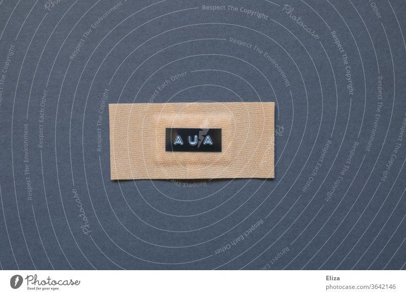 Ein Pflaster auf dem das Wort Aua steht. Konzept Schmerzen und Verletzung. geschrieben Heftpflaster Wunde Gesundheitswesen wehtun blau verwundet schmerzhaft