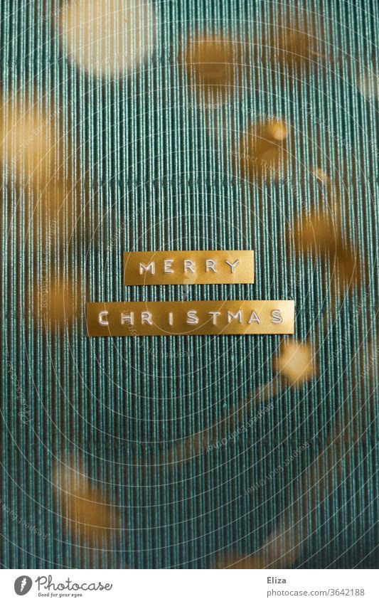 Merry Christmas. Frohe Weihnachten. Auf einem goldenen Etikett, auf blauem Hintergrund  geschrieben englisch festlich dekoriert Schrift Text weihnachtsgruß