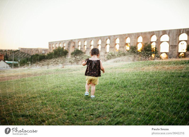 Mit Wassersprinklern spielende Kinder Sprinkleranlage Sommer Sommerurlaub Garten Park im Freien Erfrischung erfrischend Tag Freude Außenaufnahme Rasen Regen