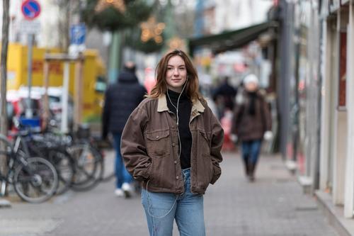 Junge Frau in Jeans und Jacke hört Kopfhörer auf dem Bürgersteig kaukasische Ethnizität Audio Musik hören Straße Freizeitkleidung Lächeln Hände in den Taschen