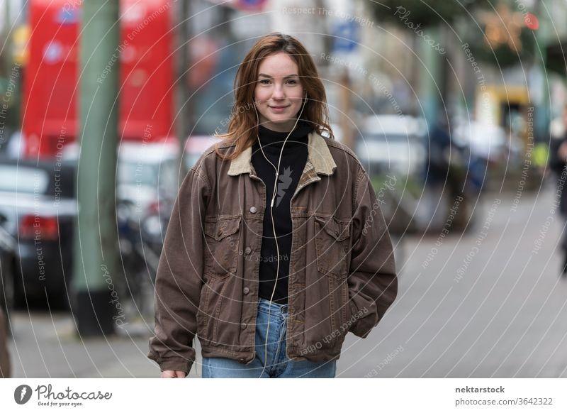 Fröhliche junge Frau hört Kopfhörer auf dem Bürgersteig kaukasische Ethnizität Audio Musik hören Straße Freizeitkleidung Lächeln Hände in den Taschen