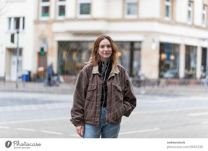 Junge Frau mit echtem Lächeln steht auf der Straße in der Stadt kaukasische Ethnizität Kopfhörer Audio Musik hören Bürgersteig Freizeitkleidung