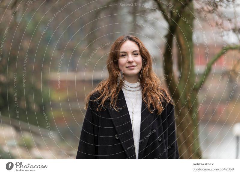 Porträt einer zwanzigjährigen kaukasischen Frau im Park kaukasische Ethnizität Kopfhörer Audio Musik hören braune Haare Modell aus dem wirklichen Leben