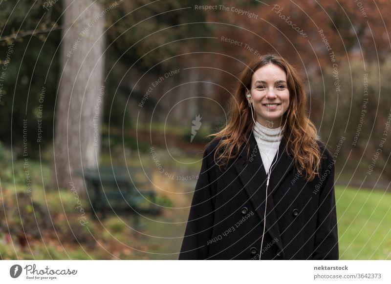 Junge Frau mit zahnbeinigem Lächeln posiert im Autumnal Park kaukasische Ethnizität Kopfhörer Audio Musik hören braune Haare Modell aus dem wirklichen Leben