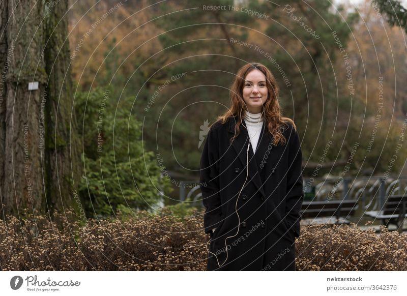Junge kaukasische Frau posiert im Herbstpark kaukasische Ethnizität Kopfhörer Audio Musik hören braune Haare Modell aus dem wirklichen Leben reales Leben
