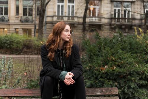 Junge kaukasische Frau sitzt mit gedrehtem Kopf auf Parkbank kaukasische Ethnizität Kopfhörer Audio Musik hören braune Haare Modell aus dem wirklichen Leben