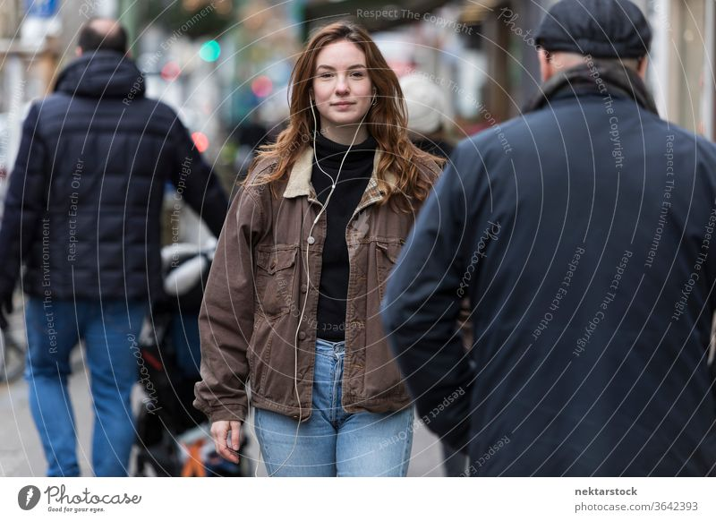 Junge Frau in Jeans und braunem Mantel geht unter Fußgängern kaukasische Ethnizität Kopfhörer Audio Musik hören Bürgersteig Straße Freizeitkleidung braune Haare