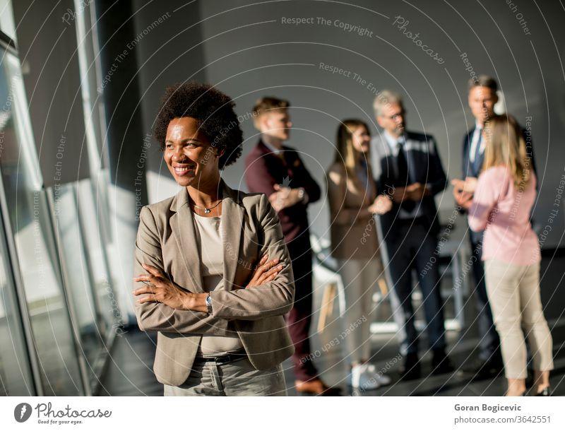 Professionelle schwarze Frau, die mit verschränkten Armen und selbstbewusstem Gesichtsausdruck im Büro steht, während andere Arbeitnehmer im Hintergrund eine Besprechung abhalten
