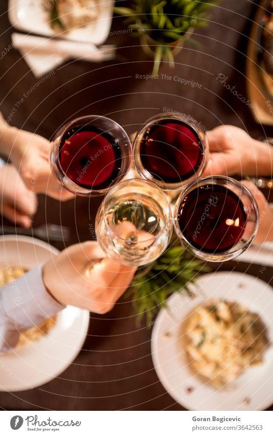 Vier Hände mit Rotwein rösten über dem servierten Tisch mit Essen rot Restaurant Party Wein Beteiligung Ansicht Top jubelt Menschen trinken Freunde Lifestyle