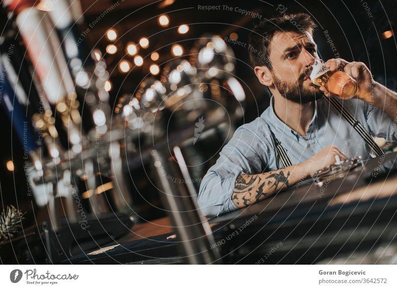 Mann trinkt Bier und raucht Zigaretten im Pub im Nachtclub Alkohol schlecht Bar Vollbart lässig Kaukasier Zigarre Konzept cool trinken betrunken Glas Typ