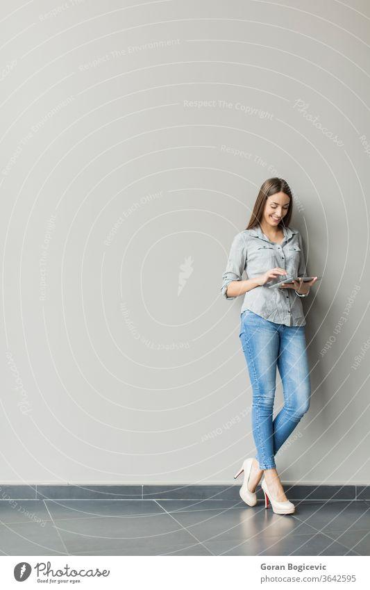 Frau mit Tablette an der Wand Erwachsener lässig Kaukasier Mitteilung Computer Zeitgenosse copyspace digital Anzeige grau gutaussehend Internet niedlich Person
