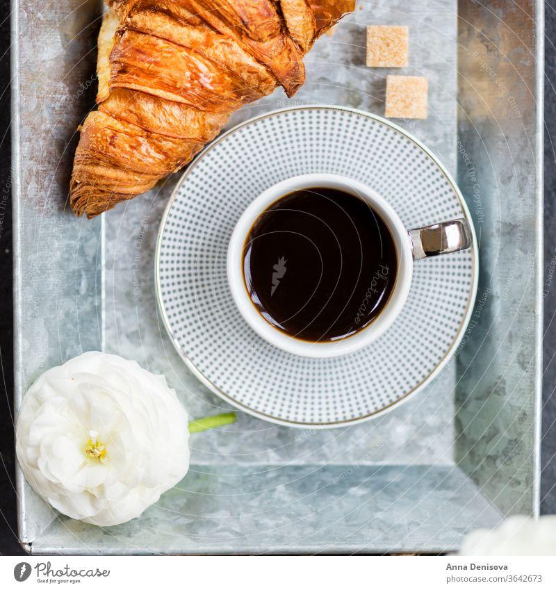 Frisches Croissant, Tasse Kaffee und Hahnenfußblüten. Frühstück Morgen Gebäck weiß Tisch Ranunculus Blumen trinken Tablett Espresso süß schwarz Cappuccino