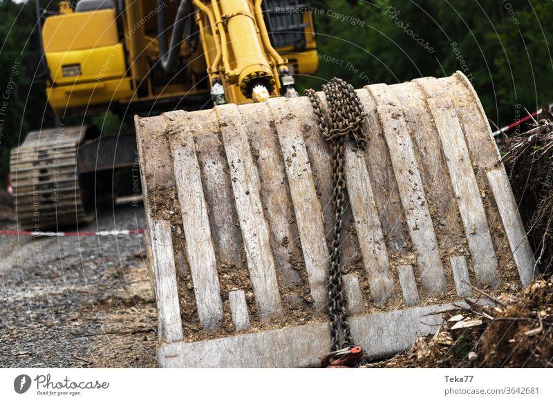 große Baggerschaufel auf einer Baustelle Großbagger gelber Bagger schaufeln große Schaufel Beton Hausbau Erde Erdbewegungsmaschine ein Haus bauen Bauarbeiten