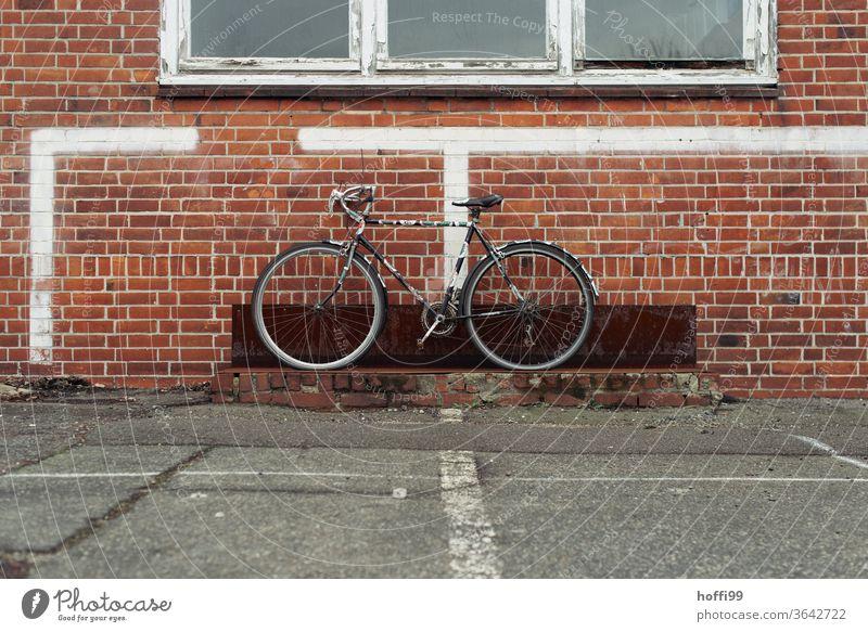 das alte Rad wartet auf Abholung - wobei es das triste Umfeld visuell erheblich bereichert. Fahrrad Fahrradständer Fahrradfahren parken Parkplatz grau 1 Reifen