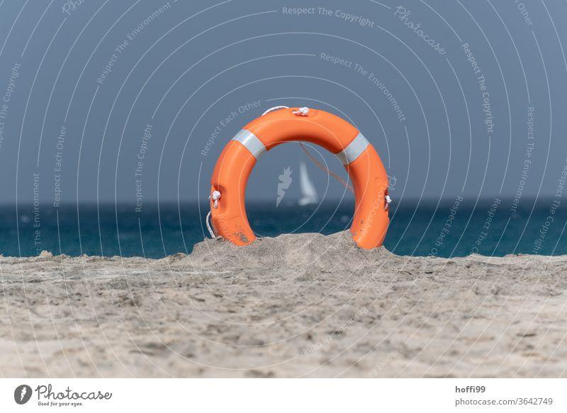 Der Blick durch den Rettungsring auf das Segelboot ist leicht verschwommen Rettungsgeräte Sandstrand Rettungsschwimmer Lebensrettung Segeln Wasser Meer