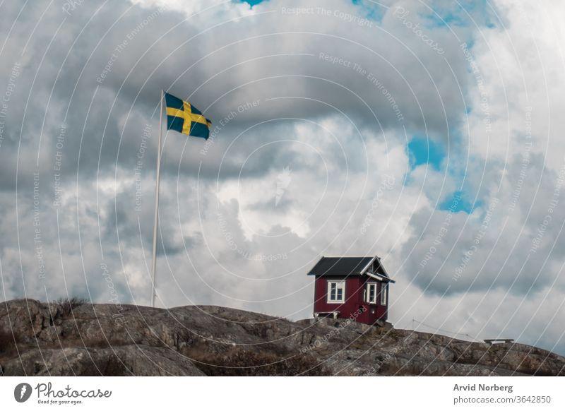 Eine traditionelle rot-weiße kleine Hütte neben der schwedischen Flagge in den südlichen Schären von Göteborg, Schweden Inselgruppe baltisch schön Schönheit