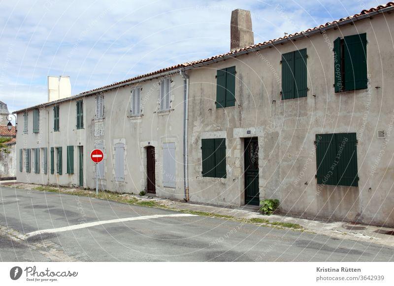 häuserzeile in saint-martin-de-ré reihenhäuser wohnhäuser altbau gebäude fassade fensterladen fensterläden geschlossen architektur straße straßenschild