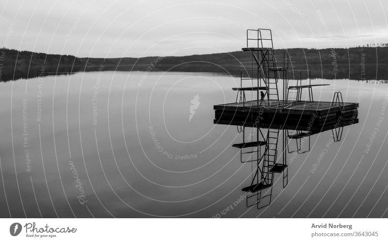 Schwarz-weißer Sprungturm mit 1, 2 und 3 Metern Höhe in einem ländlichen See in Schweden mit Spiegelung abstrakt erstaunlich Kunst Hintergrund Strand schön